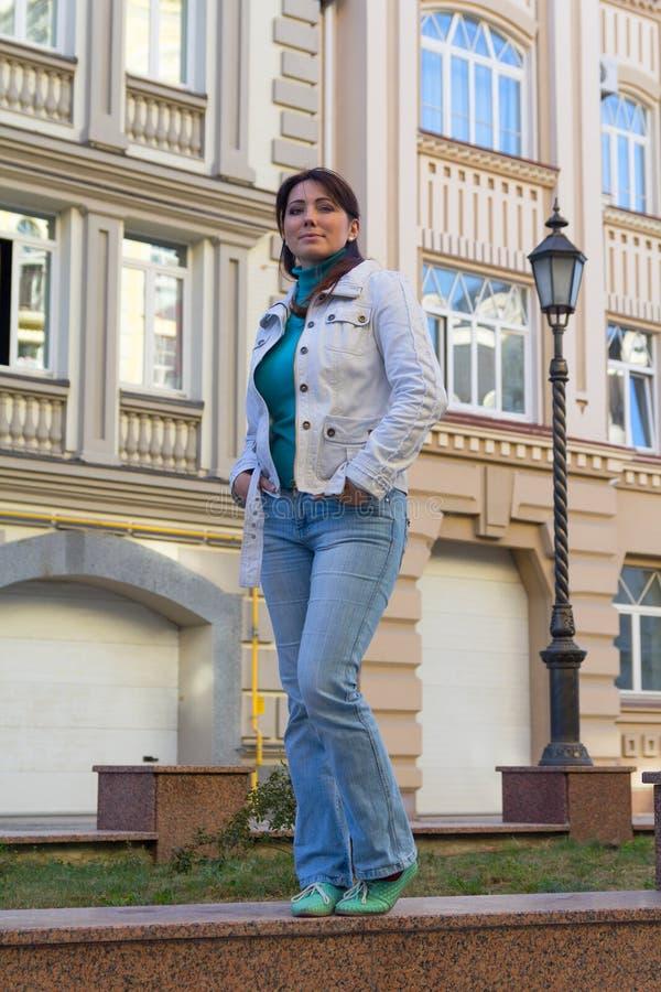 Piękna kobieta w białej kurtce na tle dom zdjęcie stock