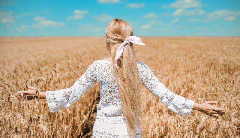 Piękna kobieta w biel ubraniach pozuje na polu zdjęcie royalty free
