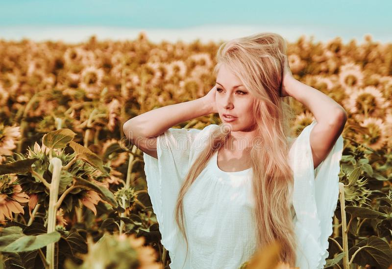 Piękna kobieta w bielu smokingowy pozować na łące z słonecznikami fotografia stock