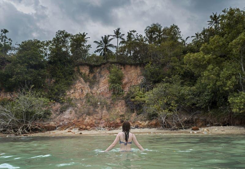 Piękna kobieta w bikini odprowadzeniu w oceanie przy tropikalną plażą fotografia stock