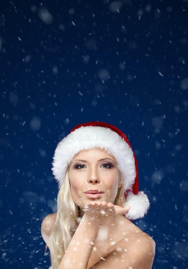 Piękna kobieta w Bożych Narodzeń nakrętki ciosów buziaku zdjęcia royalty free