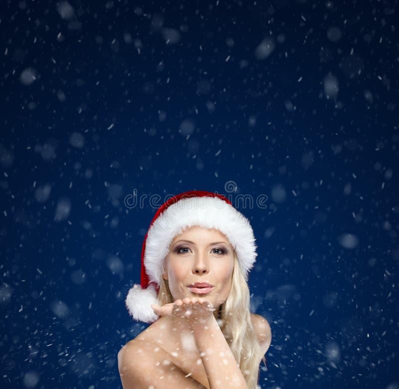 Piękna kobieta w Bożych Narodzeń nakrętki ciosów buziaku fotografia stock