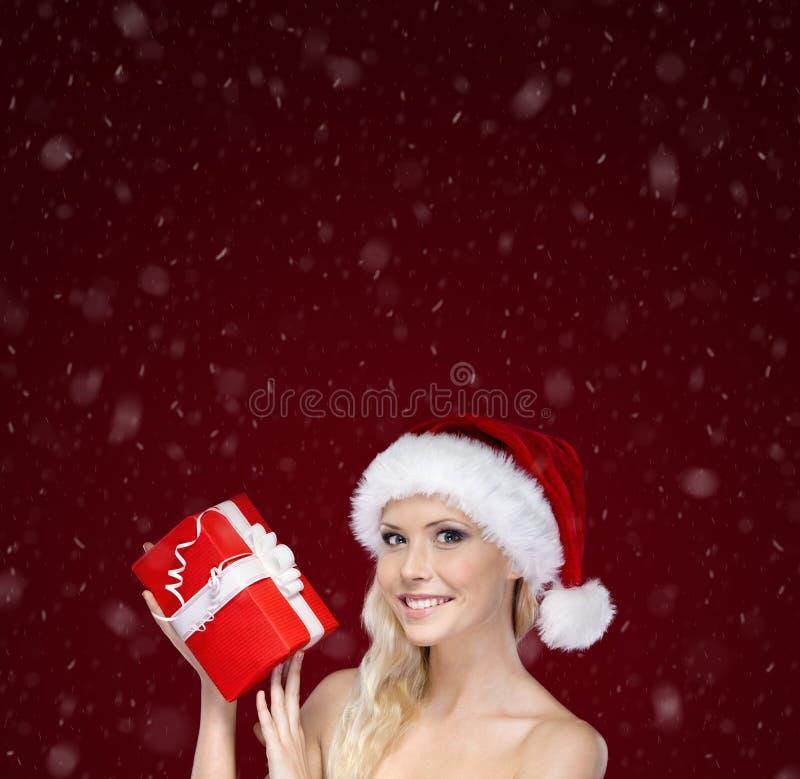 Piękna kobieta w Bożych Narodzeń nakrętki rękach teraźniejszych zdjęcia royalty free