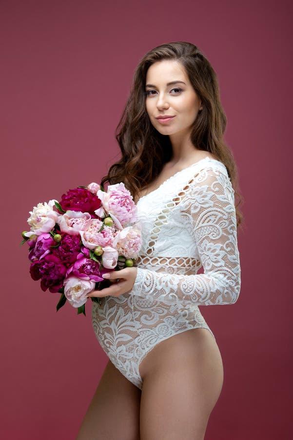 Piękna kobieta w ciąży z bukietem kwiatów peony i długimi włosami, ubrana w koronkowy biały, lacy strój fotografia stock