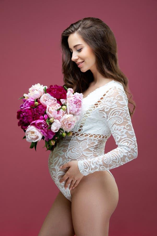 Piękna kobieta w ciąży z bukietem kwiatów peony i długimi włosami, ubrana w koronkowy biały, lacy strój zdjęcia stock