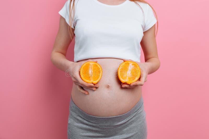 Piękna kobieta w ciąży z pomarańczową owoc na różowym tle zdjęcie royalty free