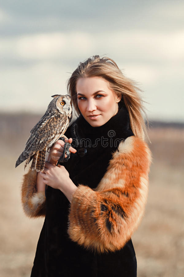 Piękna kobieta w czarnej sukni z sową na jego ręce Blondynka trzyma sowy z długie włosy w naturze Romantyczna delikatna dziewczyn fotografia royalty free