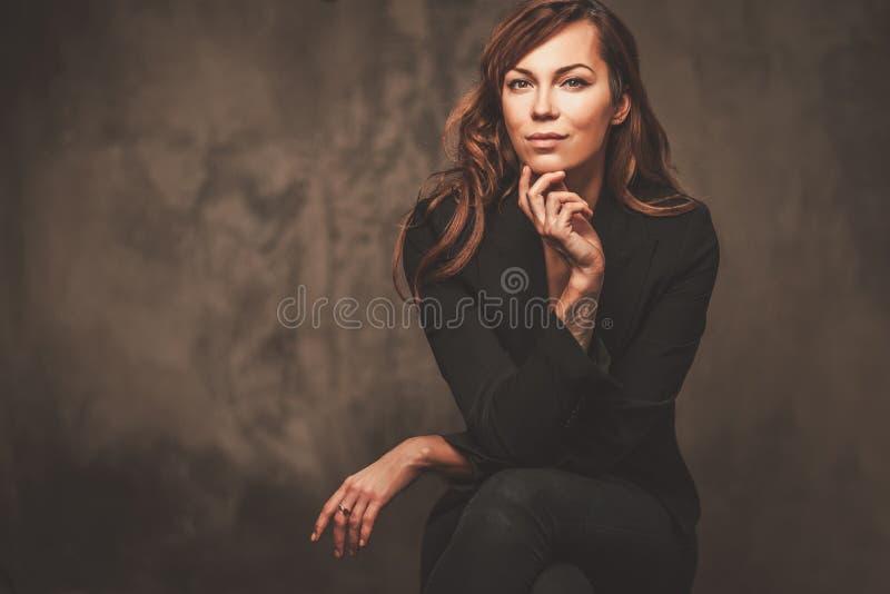 Piękna kobieta w czarnym obsiadaniu na krześle odizolowywającym na szarym tle obrazy stock