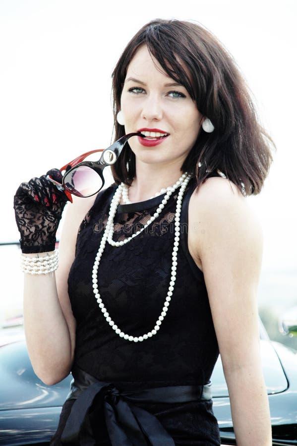 Piękna kobieta w czerń sukni i perły kolii zdjęcie stock