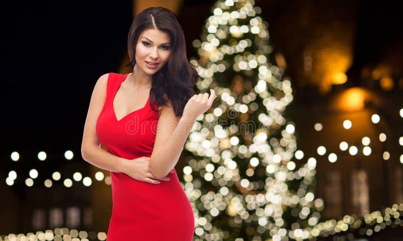Piękna kobieta w czerwieni sukni nad choinką fotografia royalty free