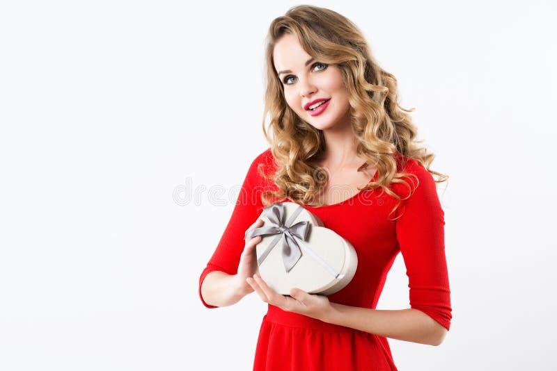 Piękna kobieta w czerwonej sukni z prezenta pudełkiem w formie serca obraz stock