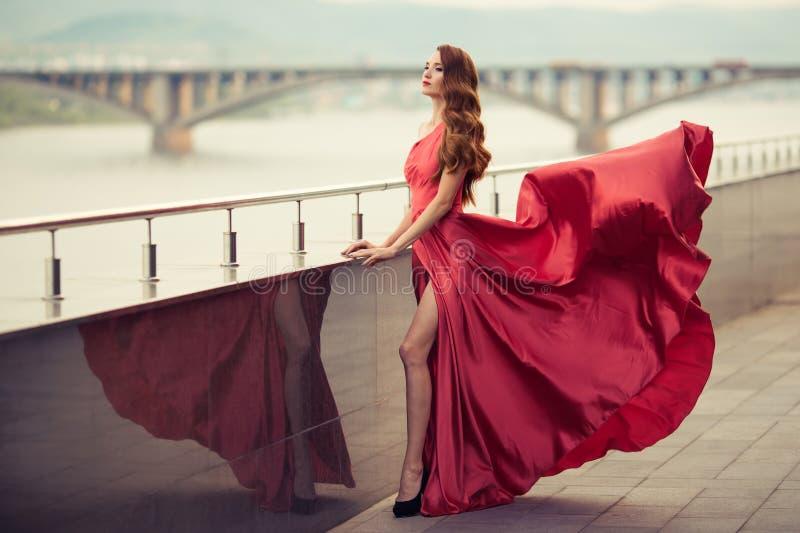Piękna kobieta w czerwonej trzepotliwej sukni tło miejskie obrazy stock