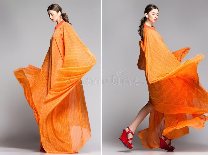 Piękna kobieta w długiej pomarańcze smokingowy pozować dramatyczny obraz stock