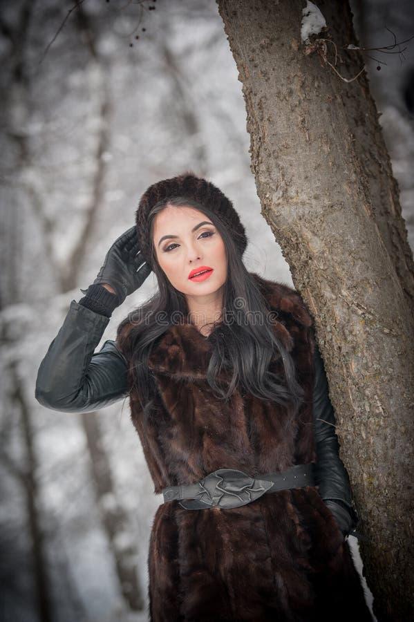 Piękna kobieta w długim czarnym futerkowym żakiecie i nakrętce cieszy się zimy scenerię w lasowy brunetki dziewczyny pozować zdjęcia royalty free