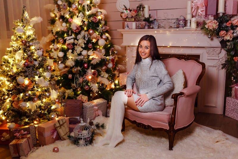 Piękna kobieta w długim grać w golfa i trykotowa suknia siedzi w różowym krześle Kobieta i boże narodzenia Delikatny Bożenarodzen zdjęcia stock