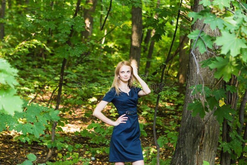 Piękna kobieta w eleganckiej sukni i powabnym uśmiechu pozuje w parku Biznesowa dziewczyna chodzi po pracy zdjęcia stock