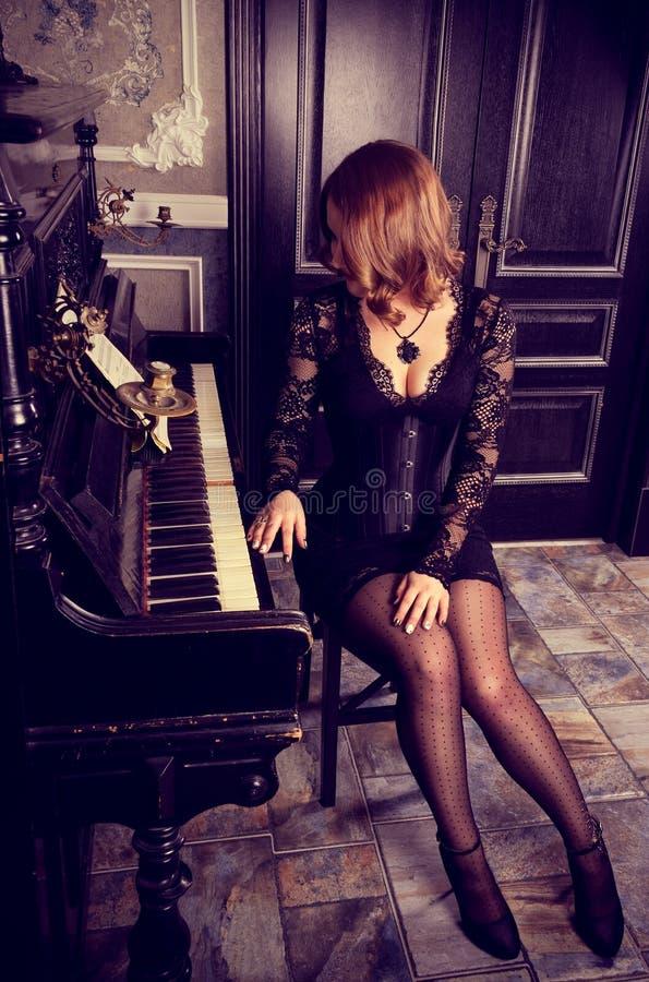 Piękna kobieta w eleganckiej sukni siedzi przy pianinem Seksowna dziewczyna w koronkowej boudoir sukni, gorseciku i Zmysłowy Retr fotografia stock