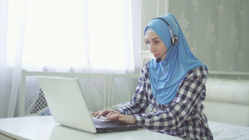Piękna kobieta w hijab przy komputerem z słuchawki w domu, daleka praca dalej obrazy stock