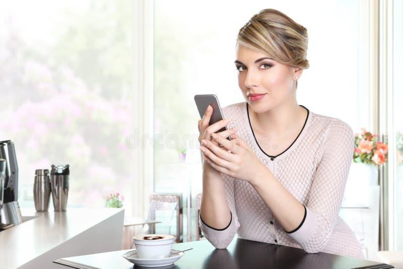 Piękna kobieta w kawie z telefonem komórkowym, napoju cappuccino obrazy stock