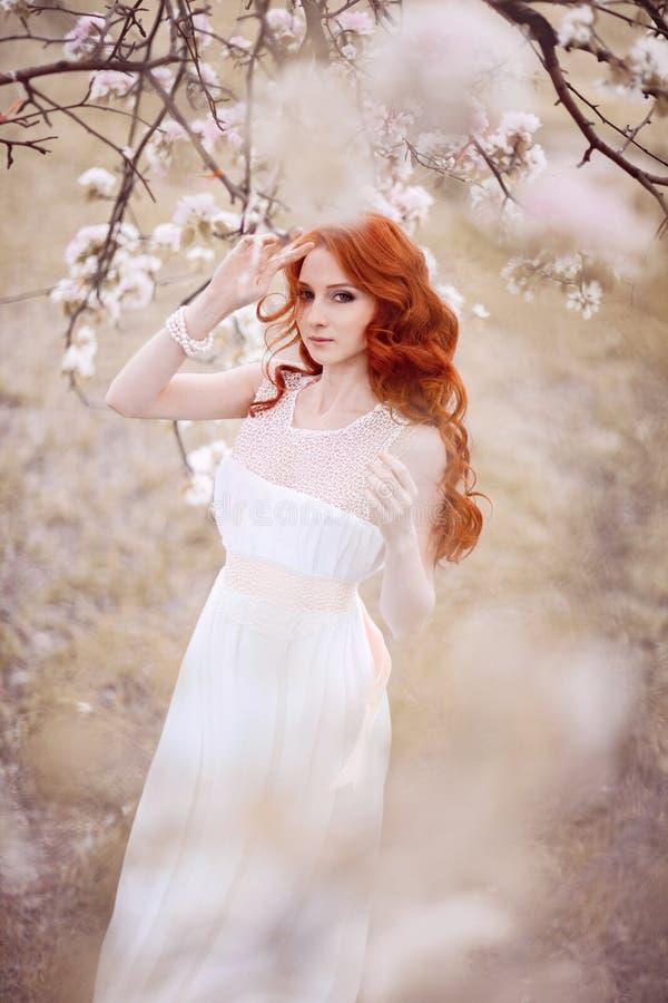 Piękna kobieta w kwiatonośnym parku fotografia stock