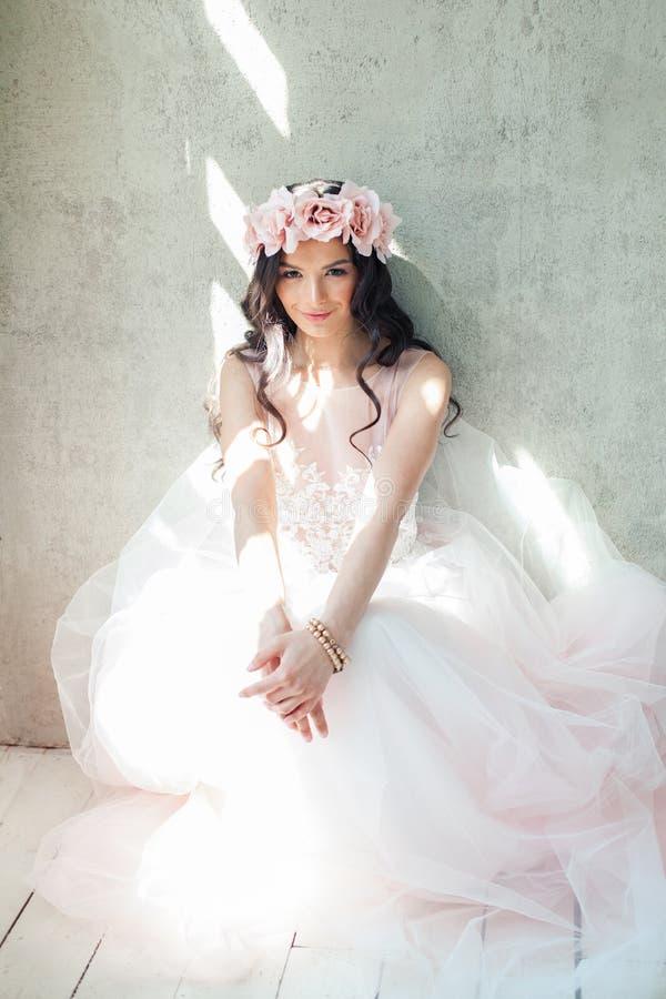 Piękna kobieta w menchii sukni i róża kwiatu wianku obraz stock