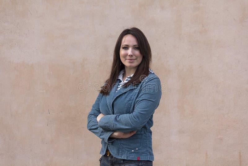 Piękna kobieta w niebieskiej marynarce na tło ścianie fotografia stock