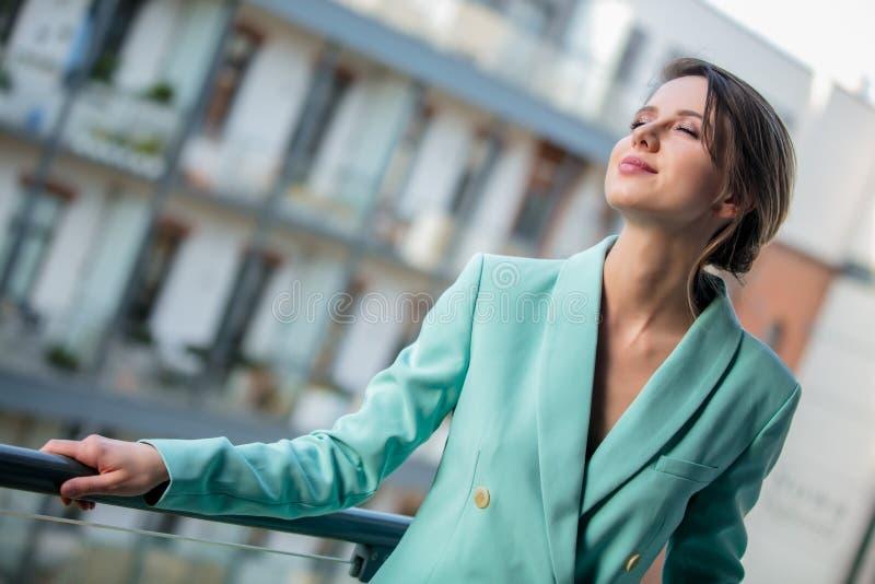 Piękna kobieta w niebieskiej marynarce przy balkonem zdjęcia royalty free