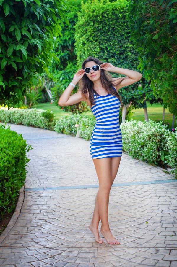 Piękna kobieta w pasiastej sukni chodzi w lato parku zdjęcie stock