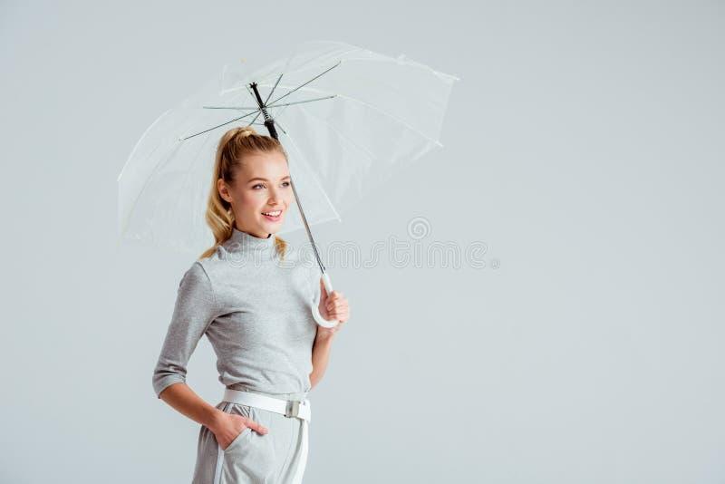 piękna kobieta w popielatych ubraniach i ręce w kieszeni pozuje z przejrzystym parasolem odizolowywającym obrazy stock