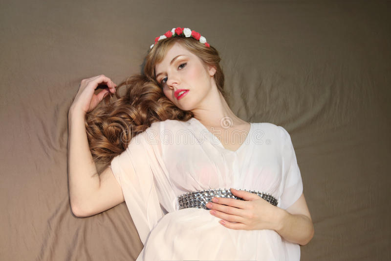Piękna kobieta w róża wianku i biel ubieramy fotografia royalty free