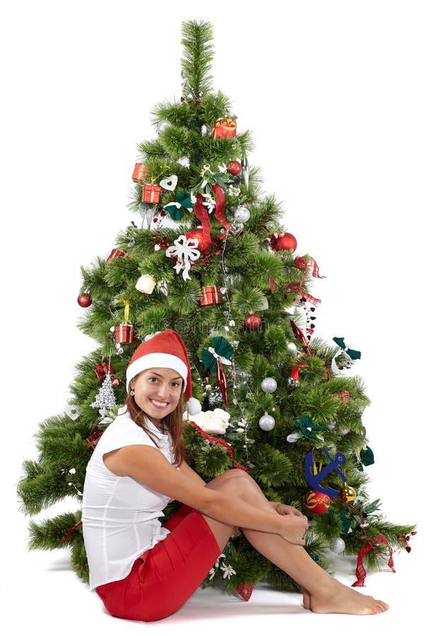 Piękna kobieta w Santa nakrętki obsiadaniu przed choinką obraz royalty free