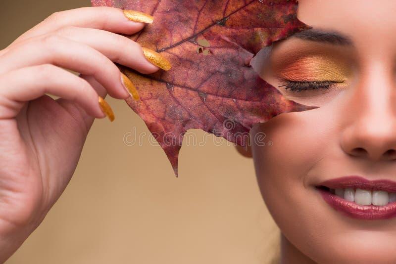 Piękna kobieta wewnątrz z jesień suchymi liśćmi obraz stock