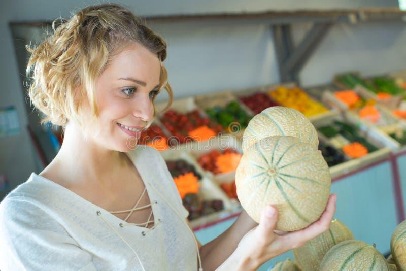 Piękna kobieta wybiera dojrzałego organicznie melon fotografia stock