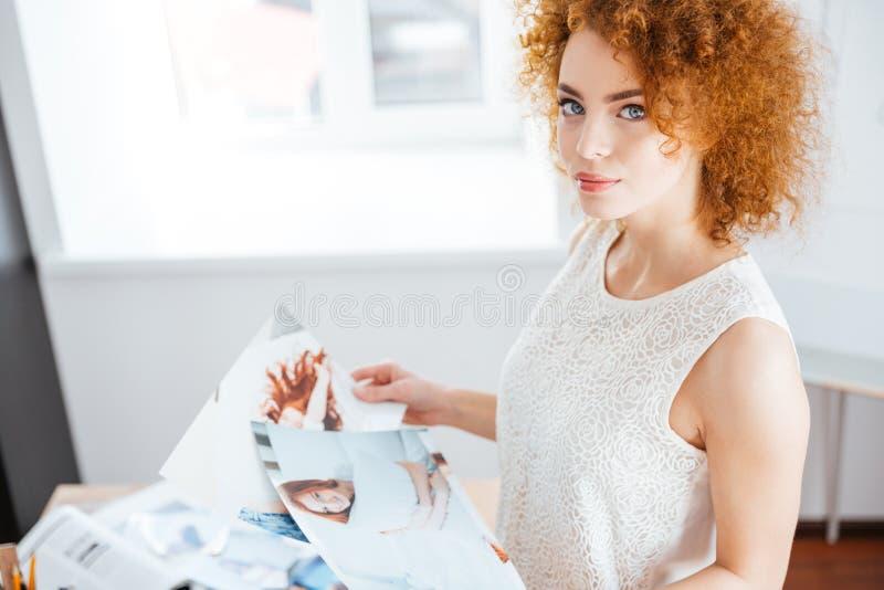 Piękna kobieta wybiera fotografie w biurze zdjęcie stock