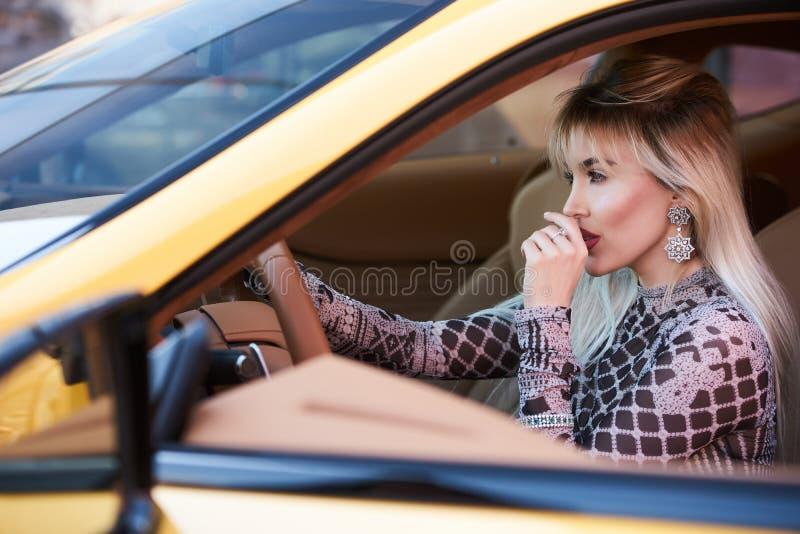 Piękna kobieta z żółtym sportowym samochodem fotografia stock