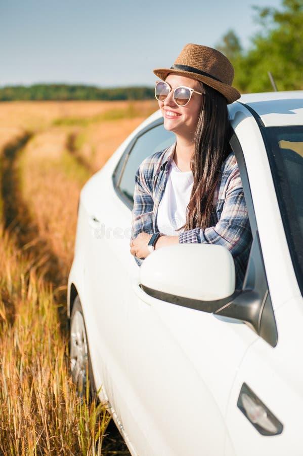 Piękna kobieta z białym samochodem w polu fotografia stock
