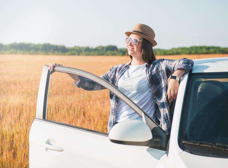 Piękna kobieta z białym samochodem w polu zdjęcia stock