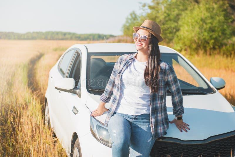 Piękna kobieta z białym samochodem w polu zdjęcie royalty free