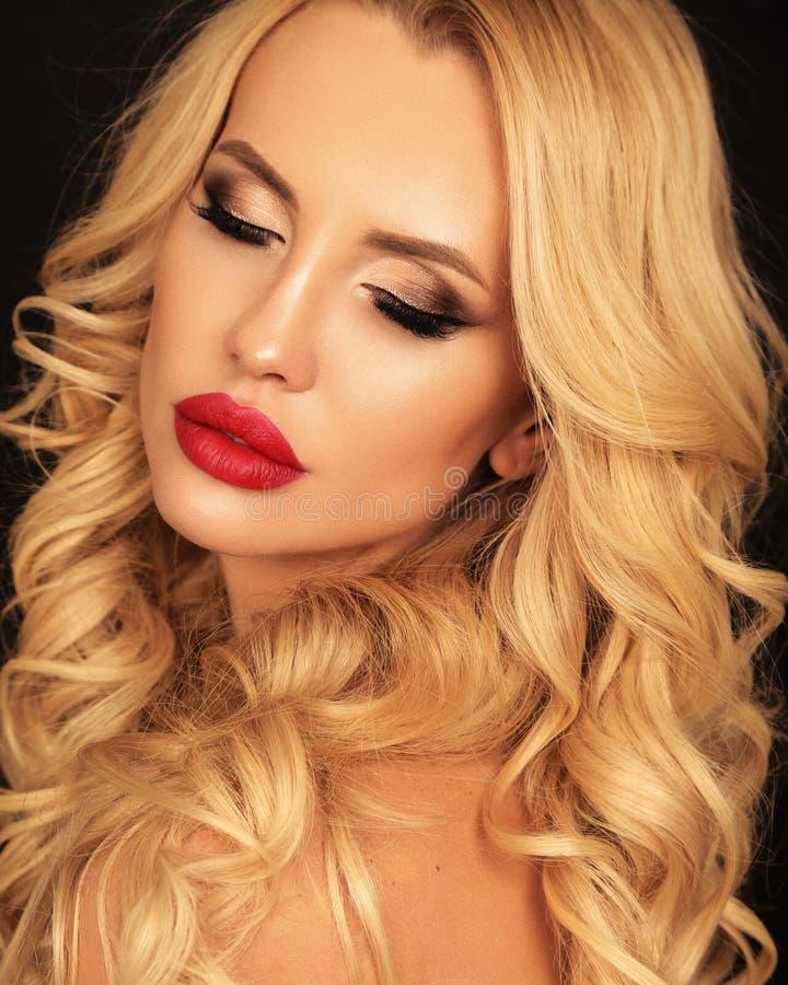 Piękna kobieta z blond kędzierzawym włosy i jaskrawym makeup pozuje i obraz stock