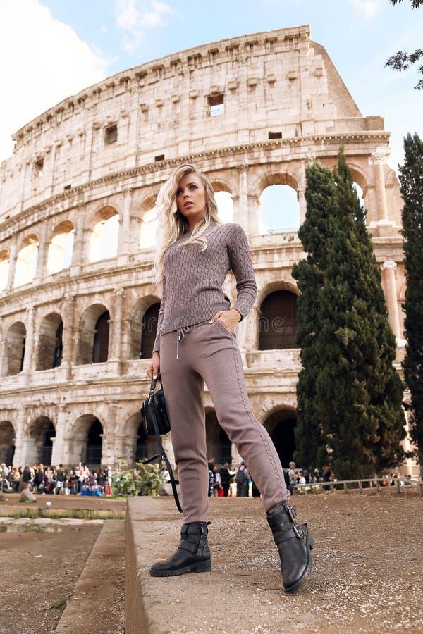 Piękna kobieta z blondynem w przypadkowy wygodnym odziewa pozować blisko Colosseum w Rzym obrazy royalty free