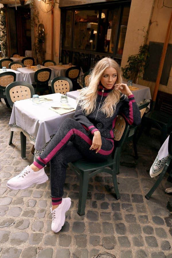 PiÄ™kna kobieta z blondynem w przypadkowym wygodnym odzieżowym obsiadaniu w wÅ'oskiej plenerowej restauracji zdjęcia stock