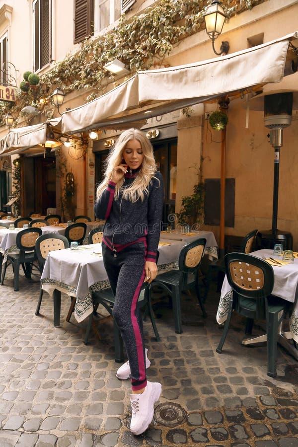 PiÄ™kna kobieta z blondynem w przypadkowym wygodnym odzieżowym obsiadaniu w wÅ'oskiej plenerowej restauracji zdjęcie stock