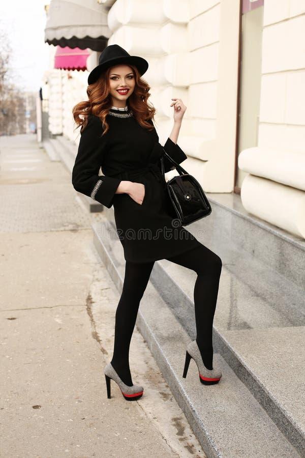 Piękna kobieta z ciemnym kędzierzawym włosy i powabnym uśmiechem, jest ubranym eleganckiego odziewa fotografia stock