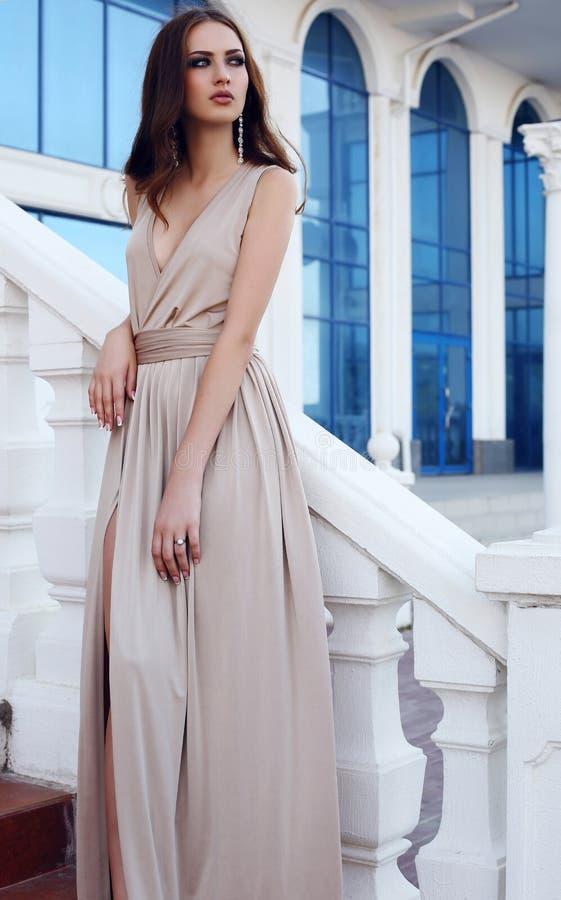 Piękna kobieta z ciemnym włosy w eleganckiej beż sukni obraz stock