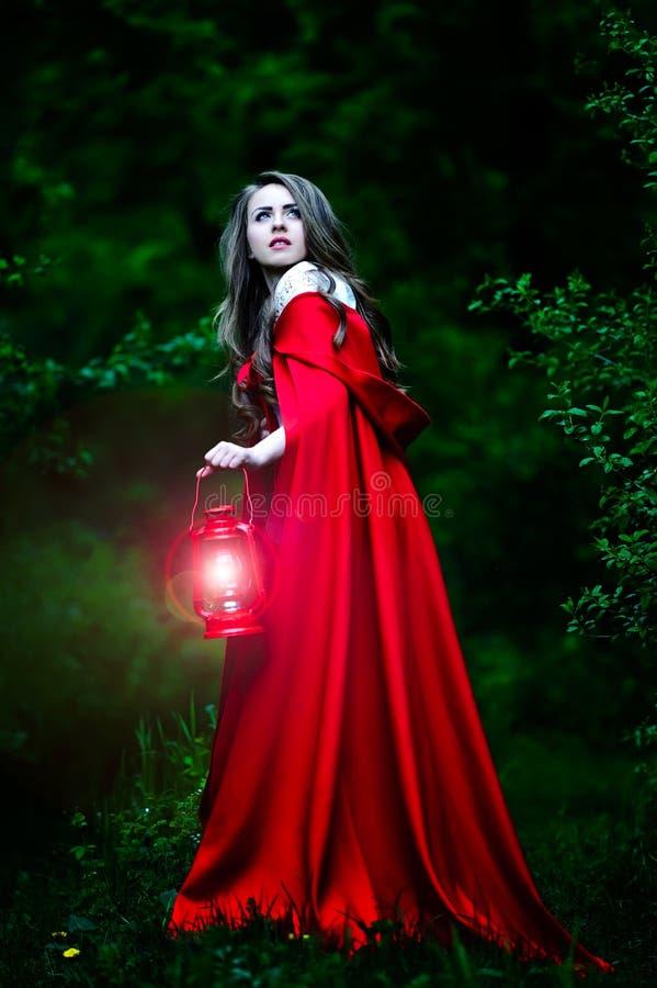 Piękna kobieta z czerwoną peleryną w drewnach obraz royalty free