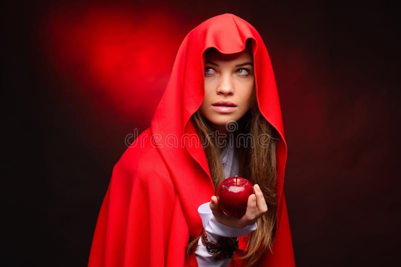 Piękna kobieta z czerwonym peleryny mienia jabłkiem w jej ręce obraz stock