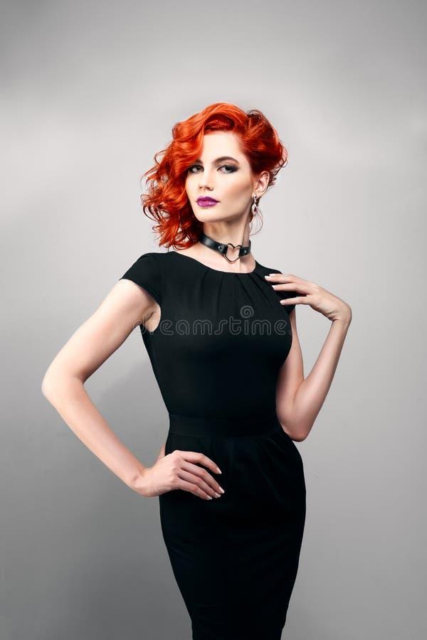 Piękna kobieta z czerwonym włosy w czarnej sukni obrazy stock