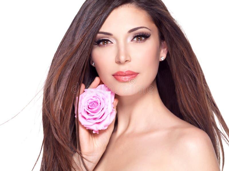 Piękna kobieta z długie włosy i wzrastał przy twarzą fotografia stock
