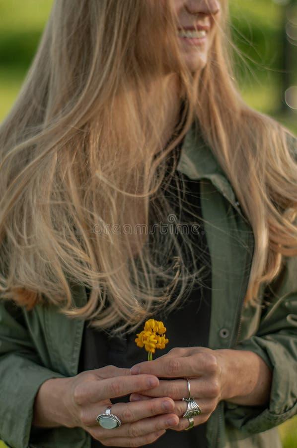 Piękna kobieta z długie włosy mienie kwiatem Ręki z pierścionku boho eleganckimi akcesoriami ?adny ostro?? zdjęcia royalty free