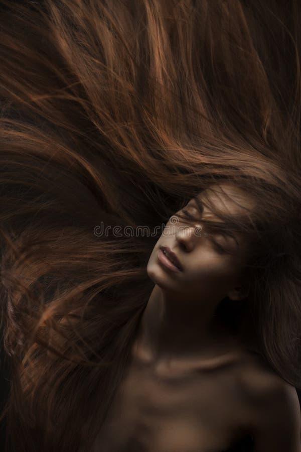 Piękna kobieta z długie włosy na ciemnym tle obraz royalty free